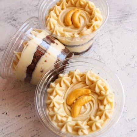 На фотографии десерт Банановый в стаканчике, шоколадный бисквит с заварным кремом, производитель кондитерских изделий под заказ Шарлотка.