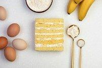 На фото бананы, яйца, крем, бисквит, ингредиенты для бананового торта, производитель кондитерских изделий под заказ Шарлотка.