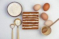 На фото яйца, крем, медовые коржи, ингредиенты для торта, производитель кондитерских изделий под заказ Шарлотка.