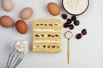 На фото вишни, яйца, крем, бисквит, ингредиенты для торта, производитель кондитерских изделий под заказ Шарлотка.