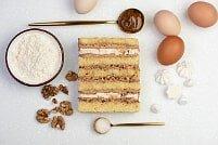 На фото орехи, яйца, крем, коржи, ингредиенты для торта, производителя кондитерских изделий под заказ Шарлотка.