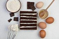 На фотографии шоколад, яйца, крем, коржи, ингредиенты для шоколадно-бананового торта, производителя кондитерских изделий под заказ Шарлотка.