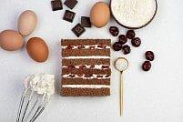 На фото кусочки шоколада, яйца, крем, бисквит, ингредиенты для торта, производитель кондитерских изделий под заказ Шарлотка.