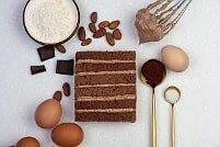 На фото шоколад, яйца, крем, коржи, ингредиенты для шоколадного торта, производителя кондитерских изделий под заказ Шарлотка.