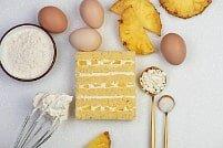 На фото кусочки ананаса, яйца, крем, бисквит, ингредиенты для торта, производителя кондитерских изделий под заказ Шарлотка.