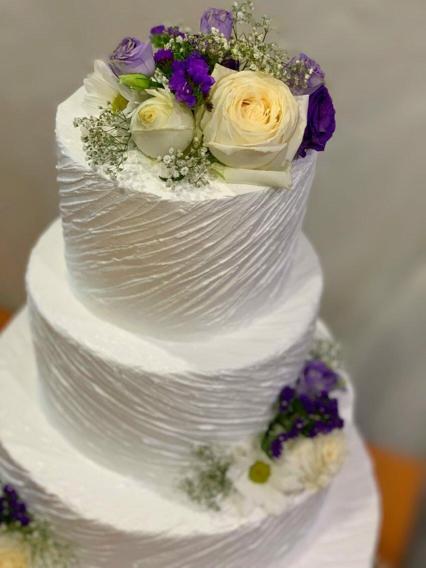 На фотографии свадебный белый торт в три яруса, украшенный цветами, производителя кондитерских изделий на заказ Шарлотка.