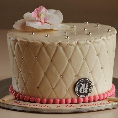 На фото круглый торт кремового цвета украшенный бусинами и цветком, производителя кондитерских изделий на заказ Шарлотка.