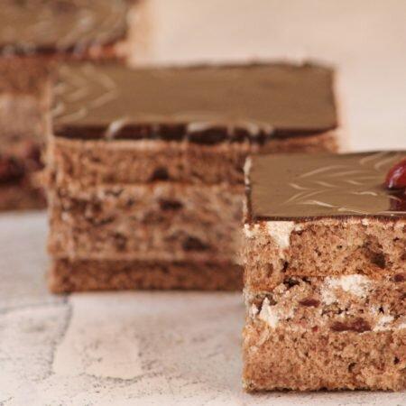 На фото торт Пьяная вишня, производителя кондитерских изделий под заказ Шарлотка, шоколадный бисквит покрытый шоколадной глазурью.