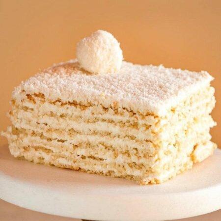 На фотографии торт Рафаэлло, производителя Шарлотка, песочные коржи с белым кремом и посыпанные кокосовой стружкой.
